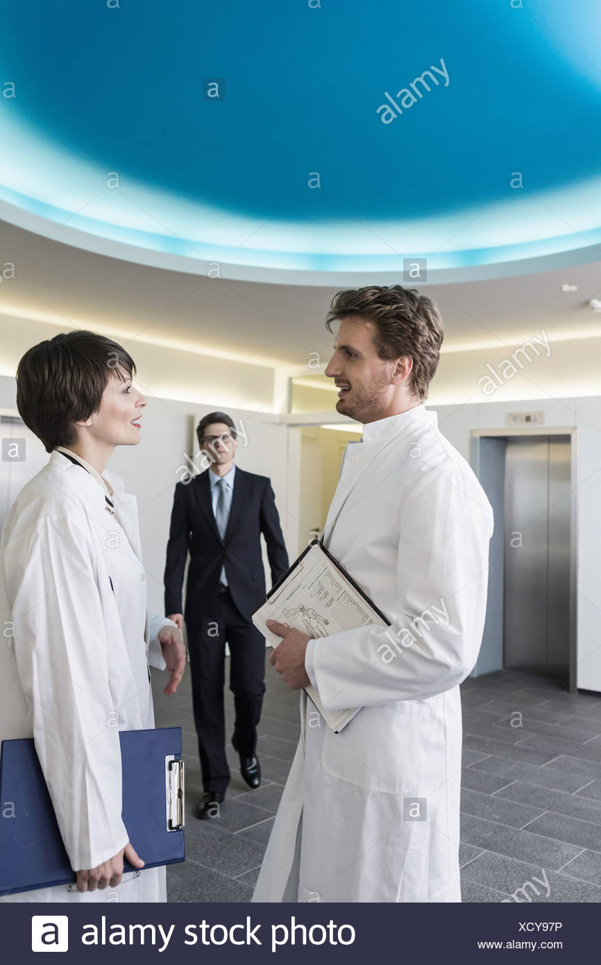 Man and woman wearing lab coats having conversation in lobby, man wearing business attire approaching - Stock Image