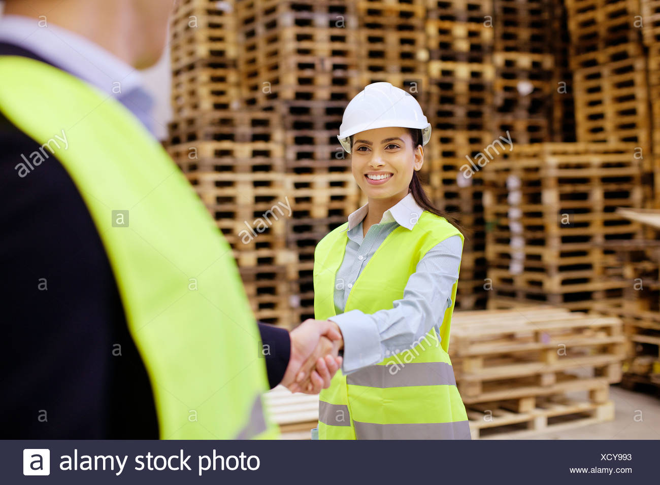 Supervisor and trainee shaking hands in distribution warehouse - Stock Image