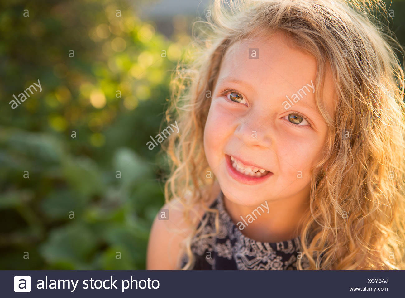A young girl with long red curly hair outdoors in a garden. - Stock Image
