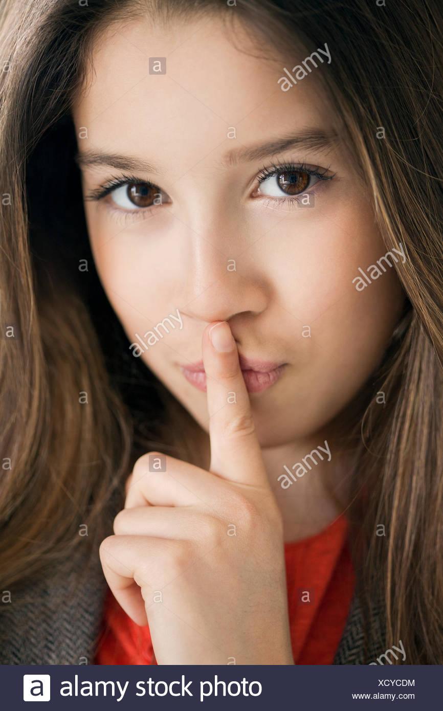 Portrait of a girl shushing - Stock Image