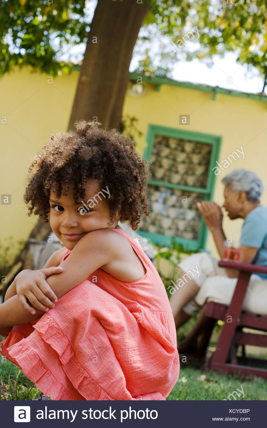 Girl crouching outdoors with people in background Stock Photo
