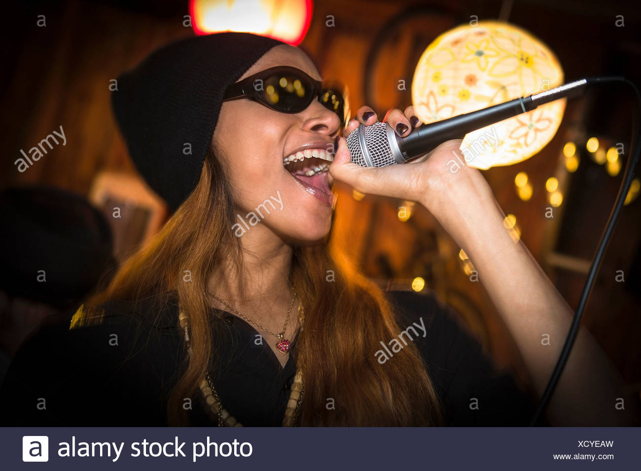 Woman wearing hat and sunglasses singing in microphone Stock Photo