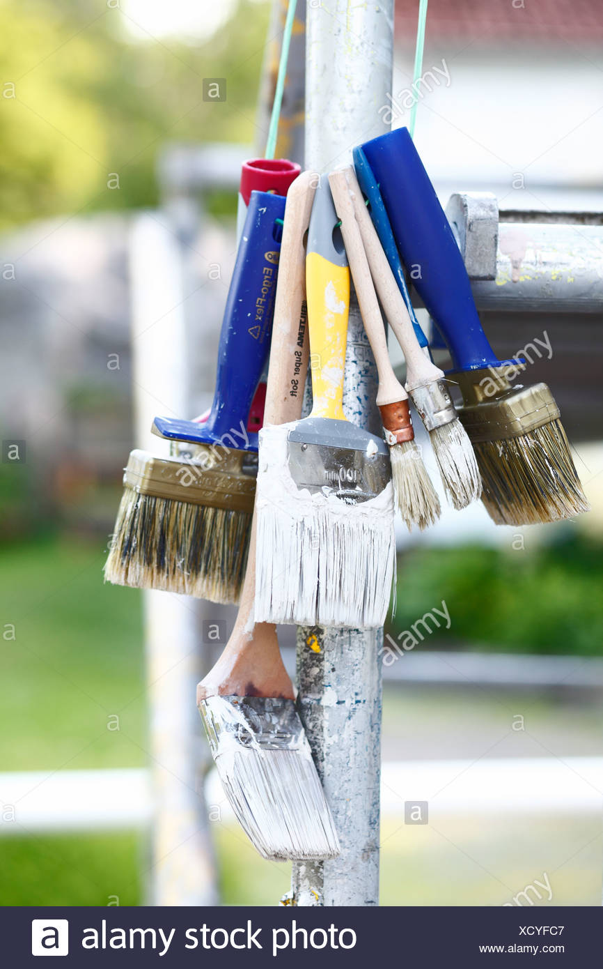 Paint brushes hanging on metal scaffolding - Stock Image
