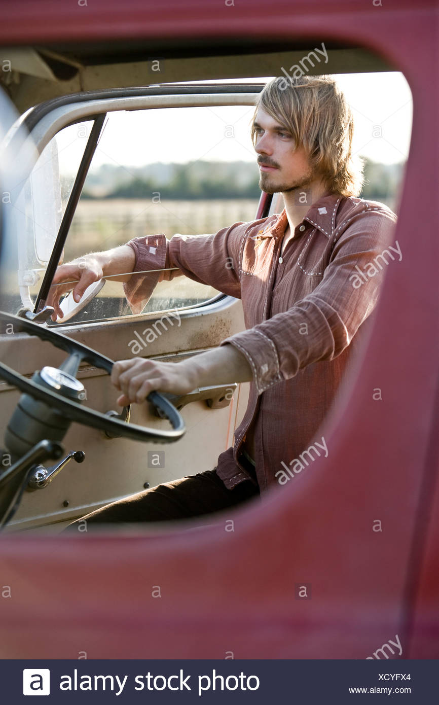 Young man climbing in van, 1970s style Stock Photo