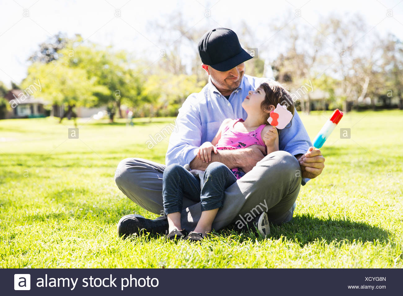 Mid adult man and daughter eating ice lollies in park Stock Photo