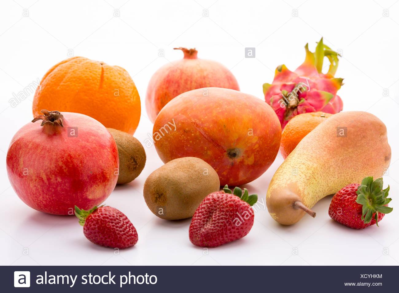 Exotic and domestic fruits: mango, two pomegranates, one pitaya, two kiwifruits, a pear, three garden strawberries and one mandarin. - Stock Image