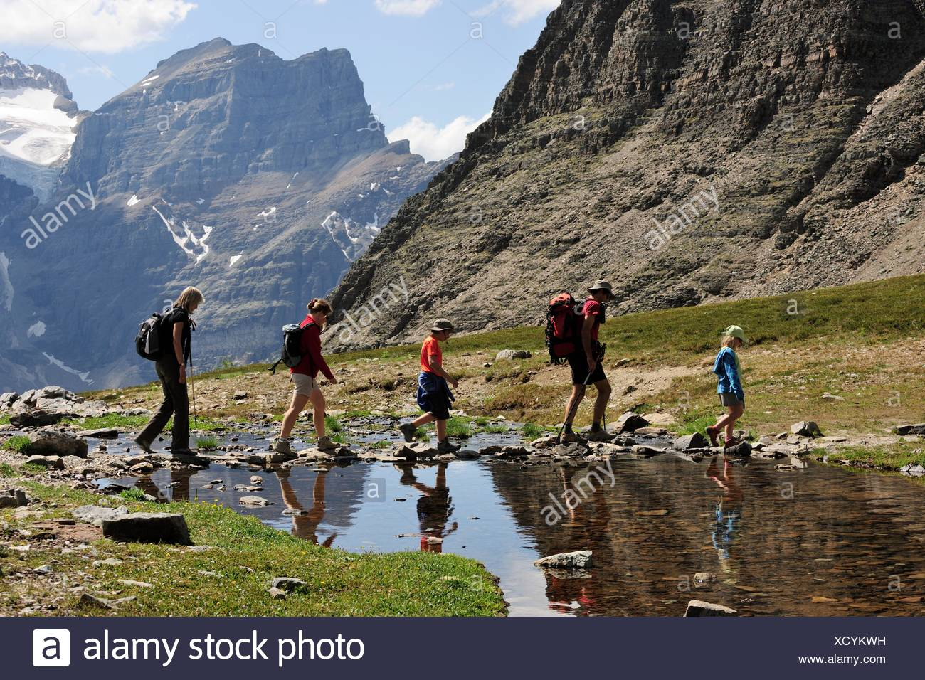 Hiker rambling in the Rocky Mountains crossing a small lake, Banff National Park, Alberta Province, Canada - Stock Image