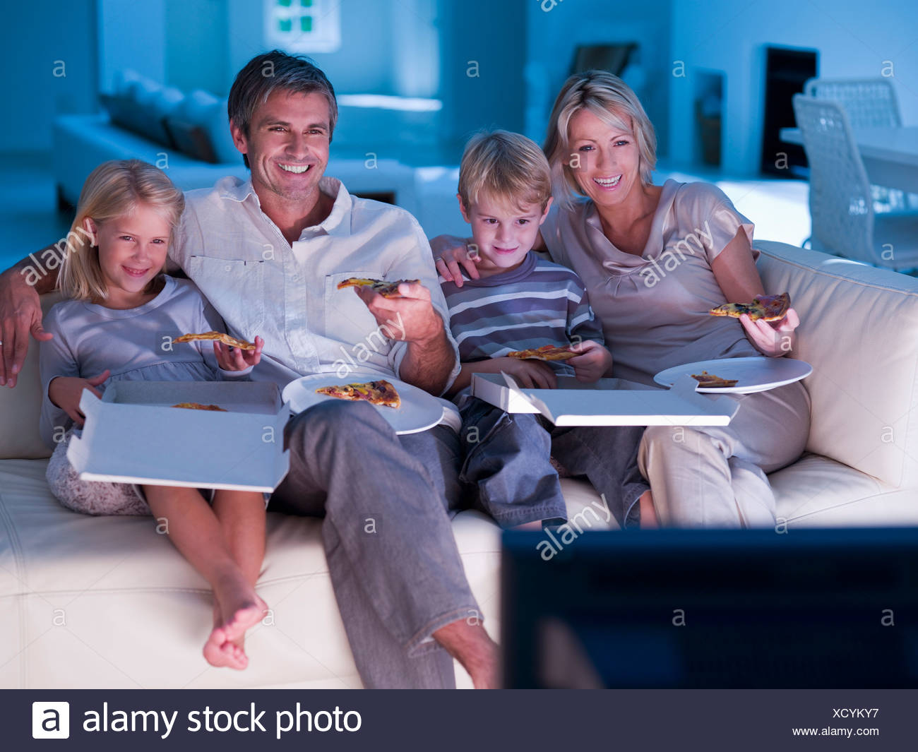 Family eating pizza and watching TV on sofa - Stock Image