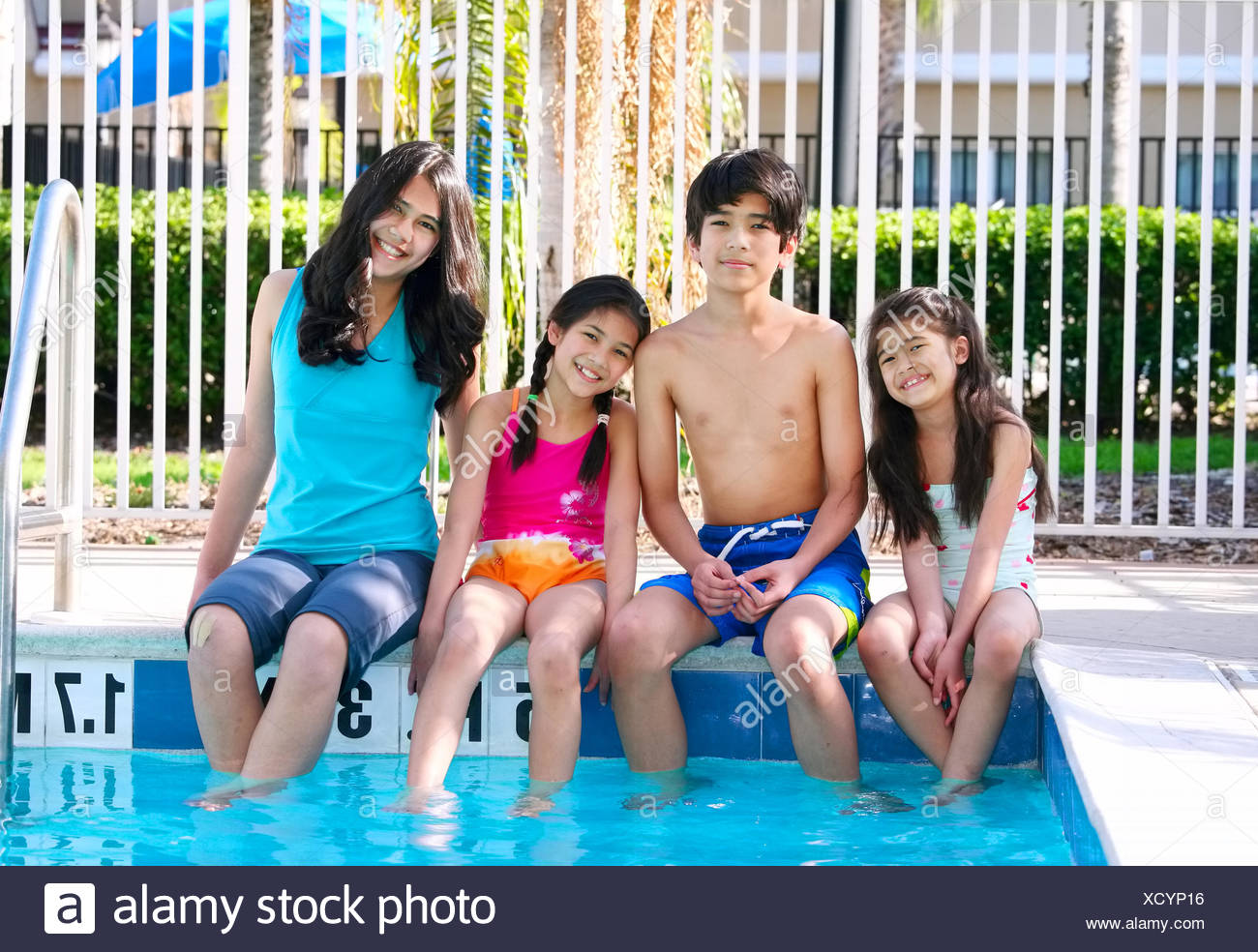 Four children, siblings, enjoying the pool together - Stock Image