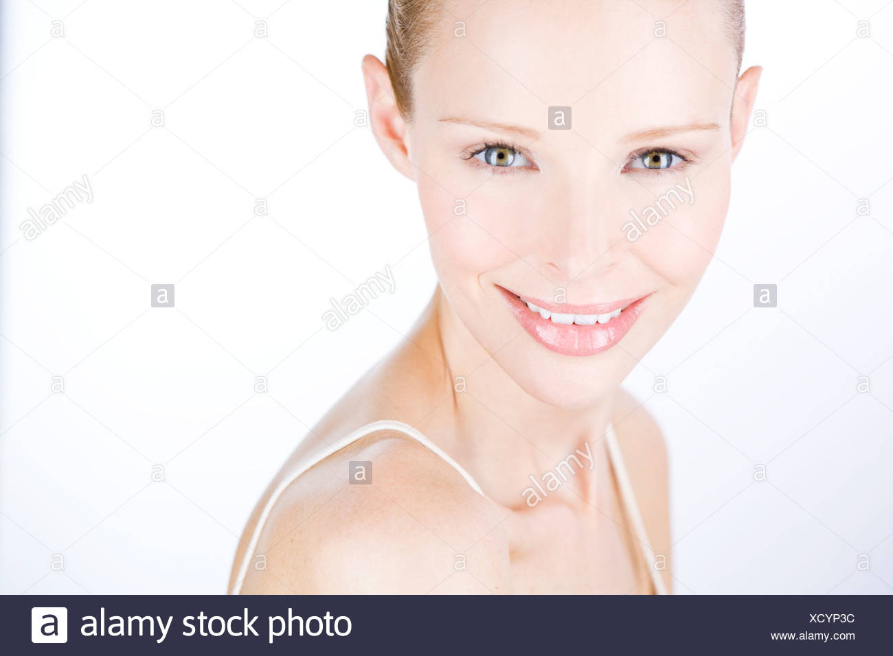 A portrait of a young woman looking over her shoulder, smiling - Stock Image