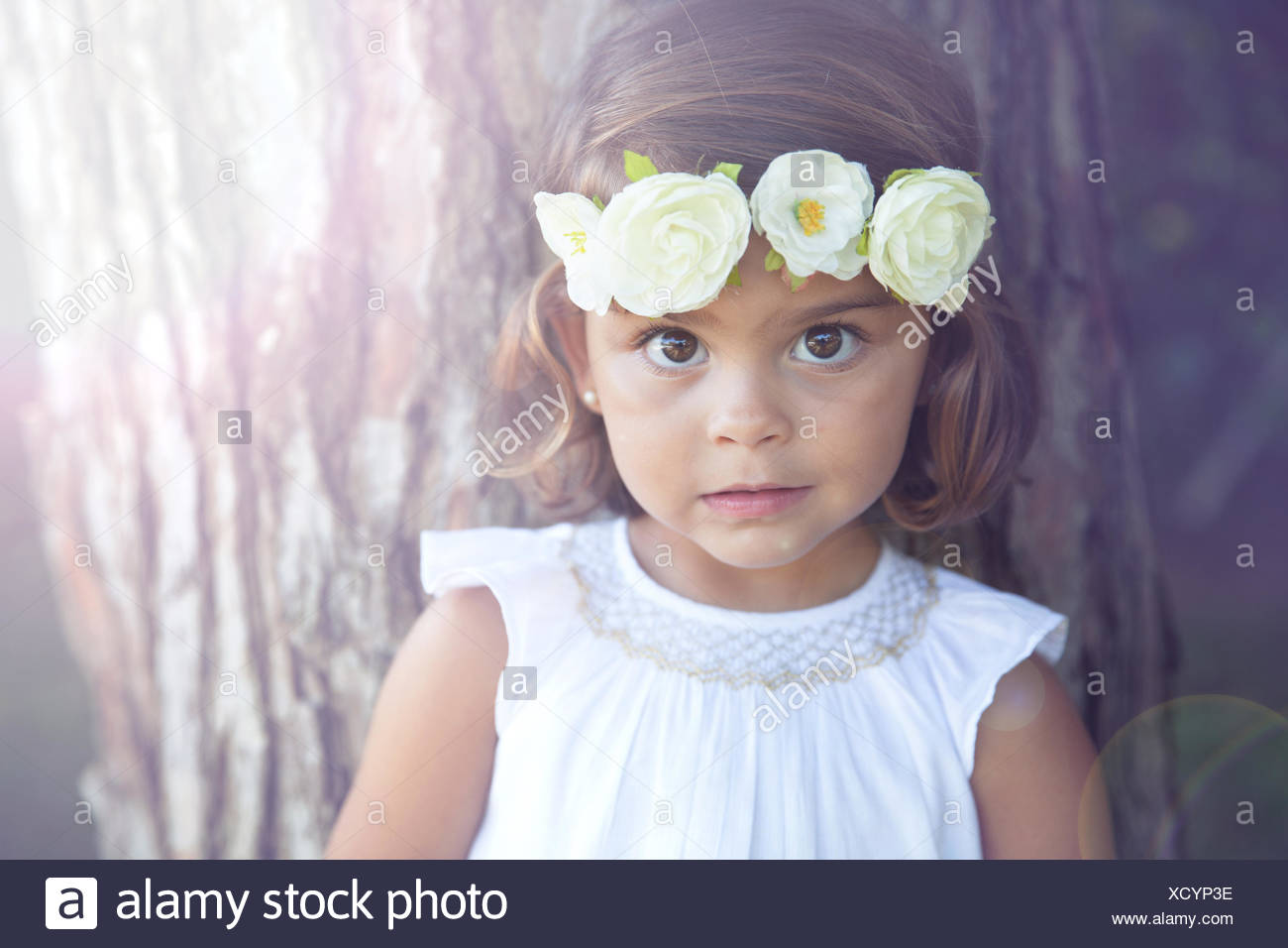 Portrait of a smiling girl wearing a flower headdress - Stock Image