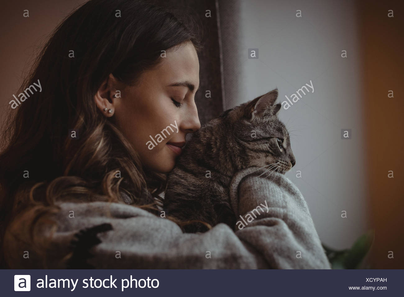 Close-up of beautiful woman smelling her pet cat - Stock Image