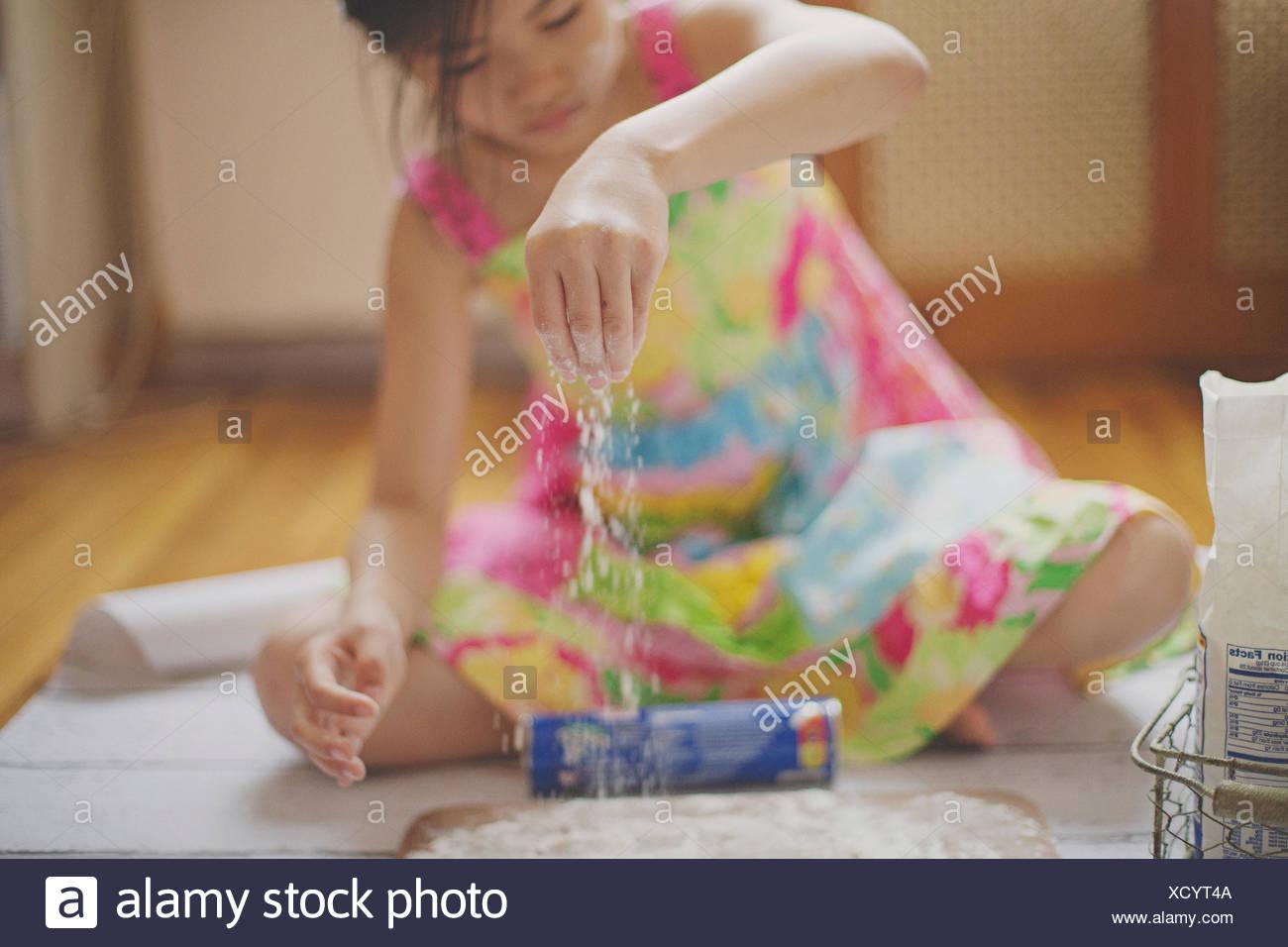 Girl sitting on the floor baking - Stock Image