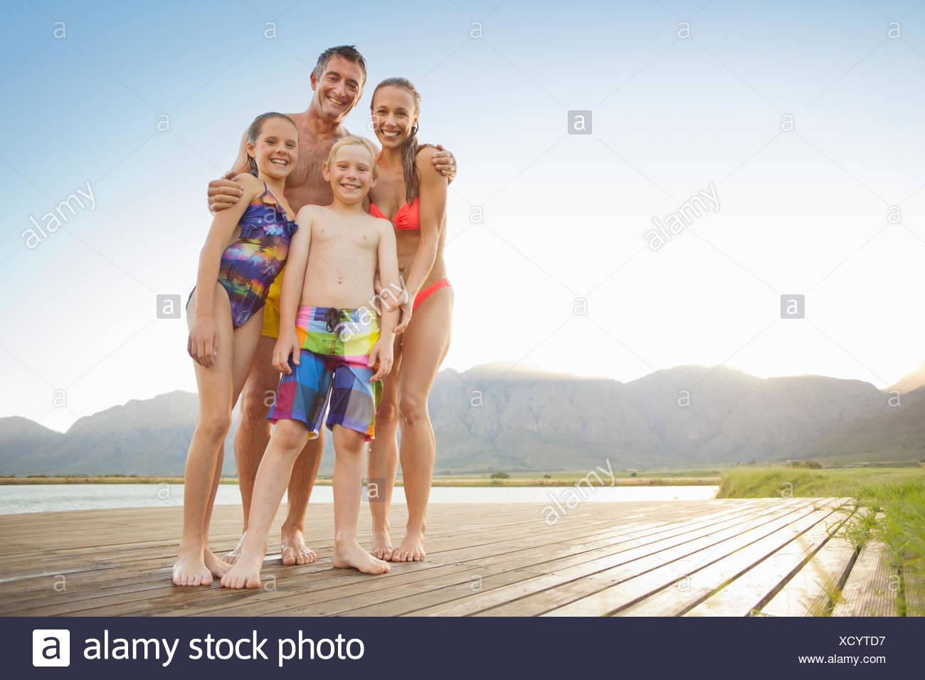 Family in swimwear on wooden jetty - Stock Image