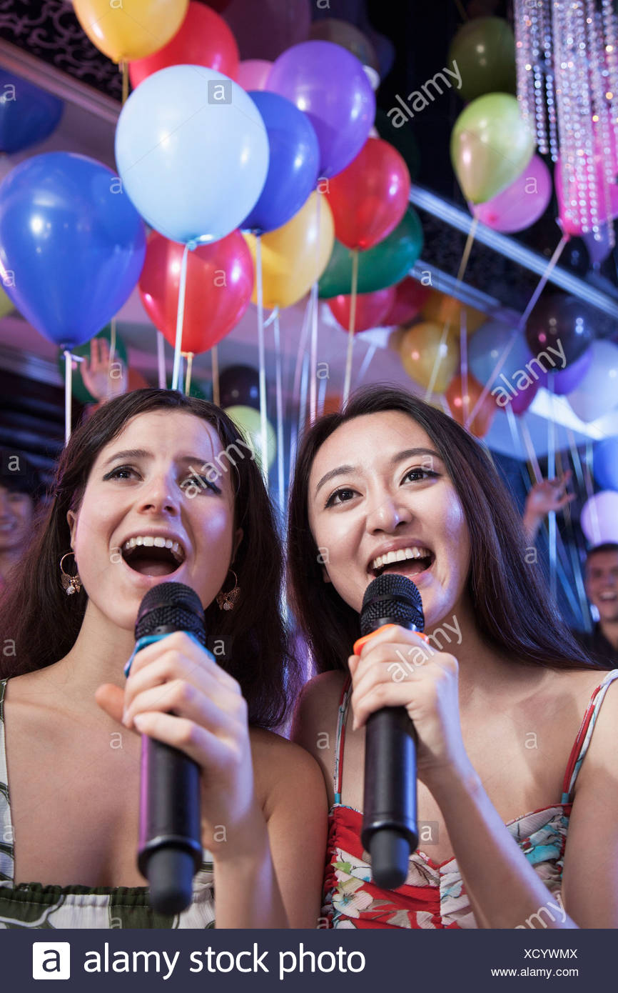 Two friends holding microphones and singing together at karaoke, balloons in the background - Stock Image