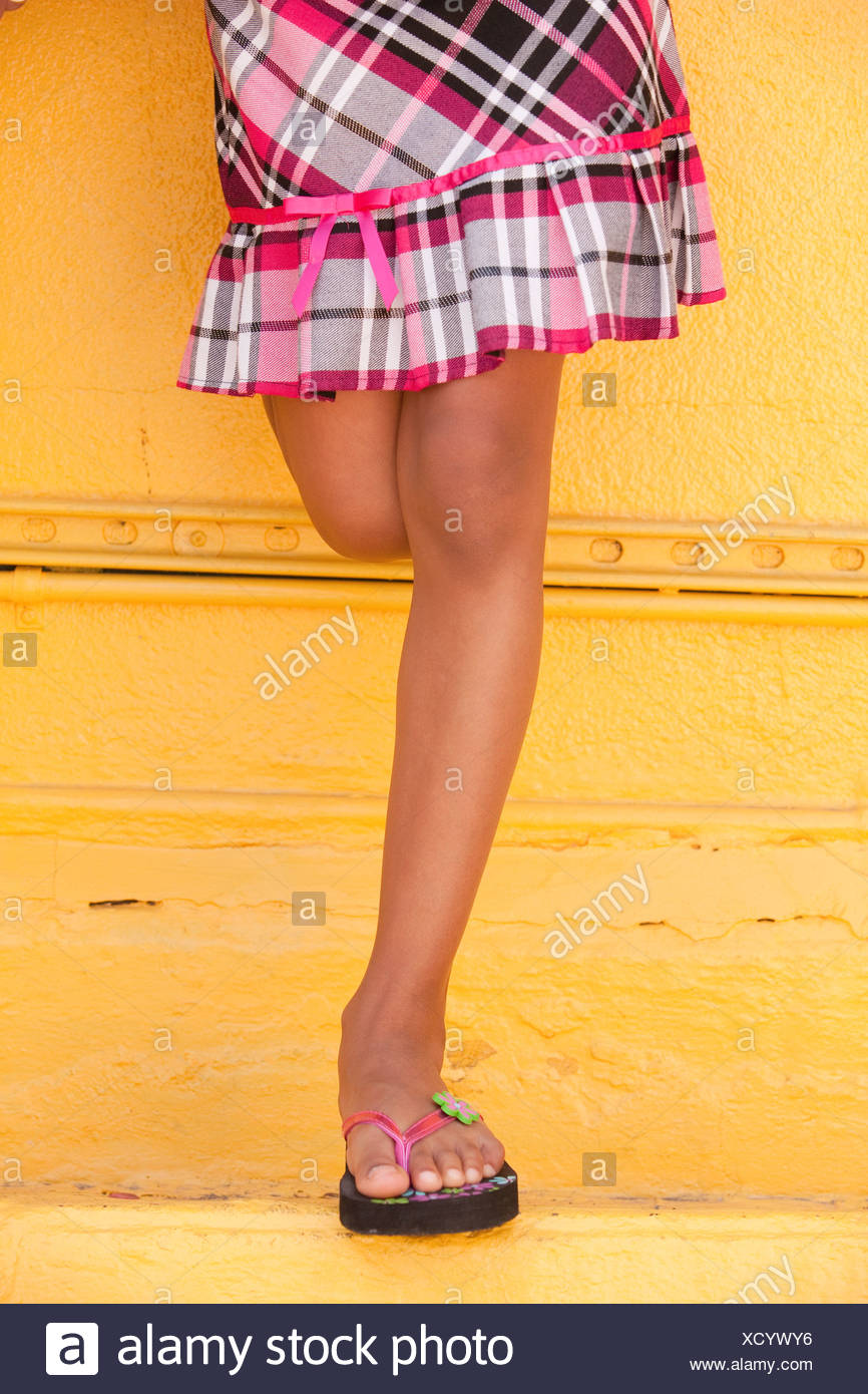 Low section view of a Hispanic girl standing in front a wall, Boston, Massachusetts, USA - Stock Image