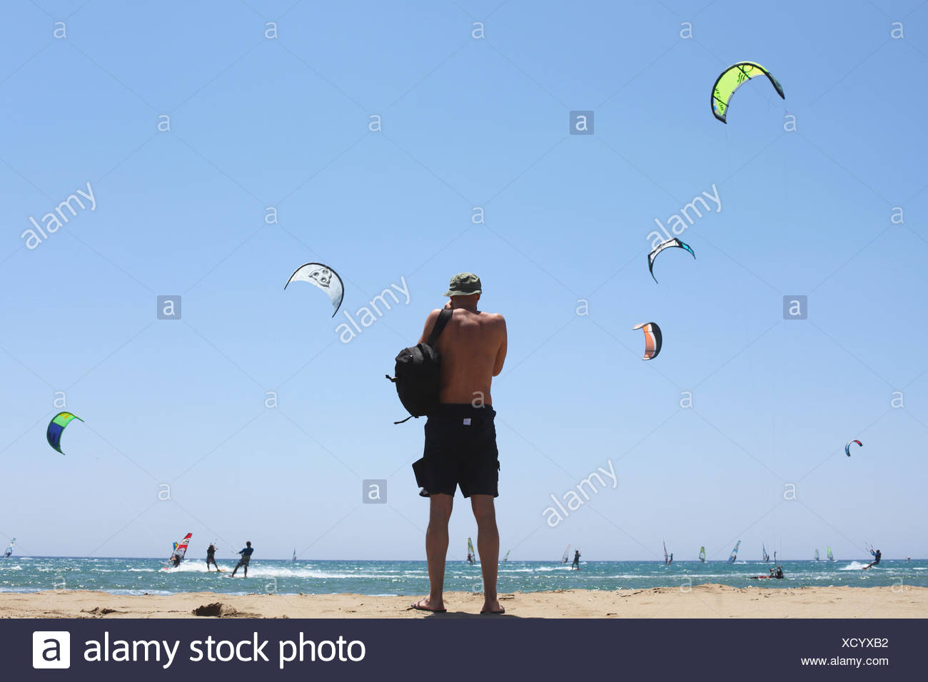 Greece, rear view of man standing on beach and looking at kites - Stock Image