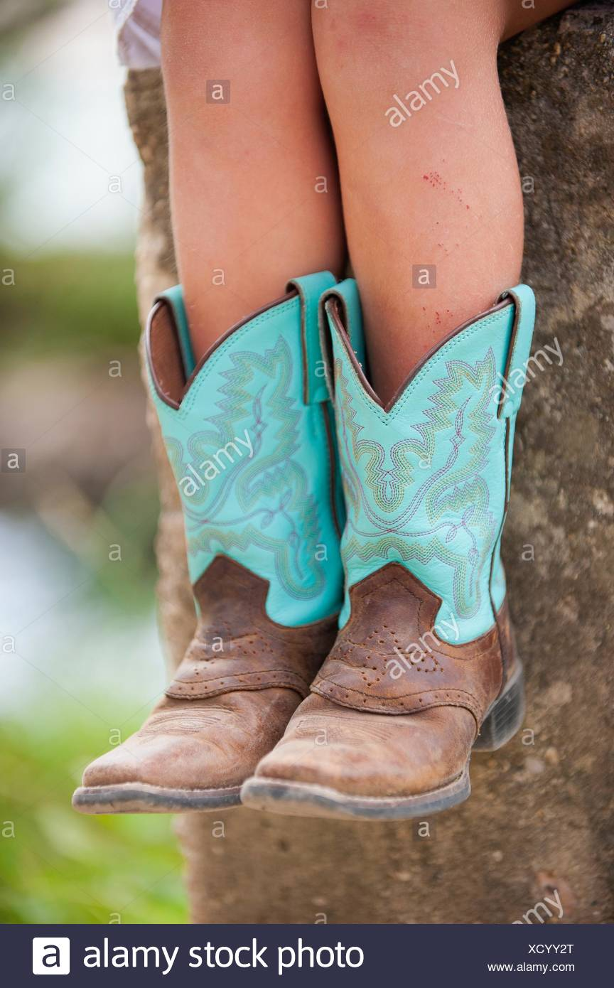 Young girls legs in cowboy boots Stock