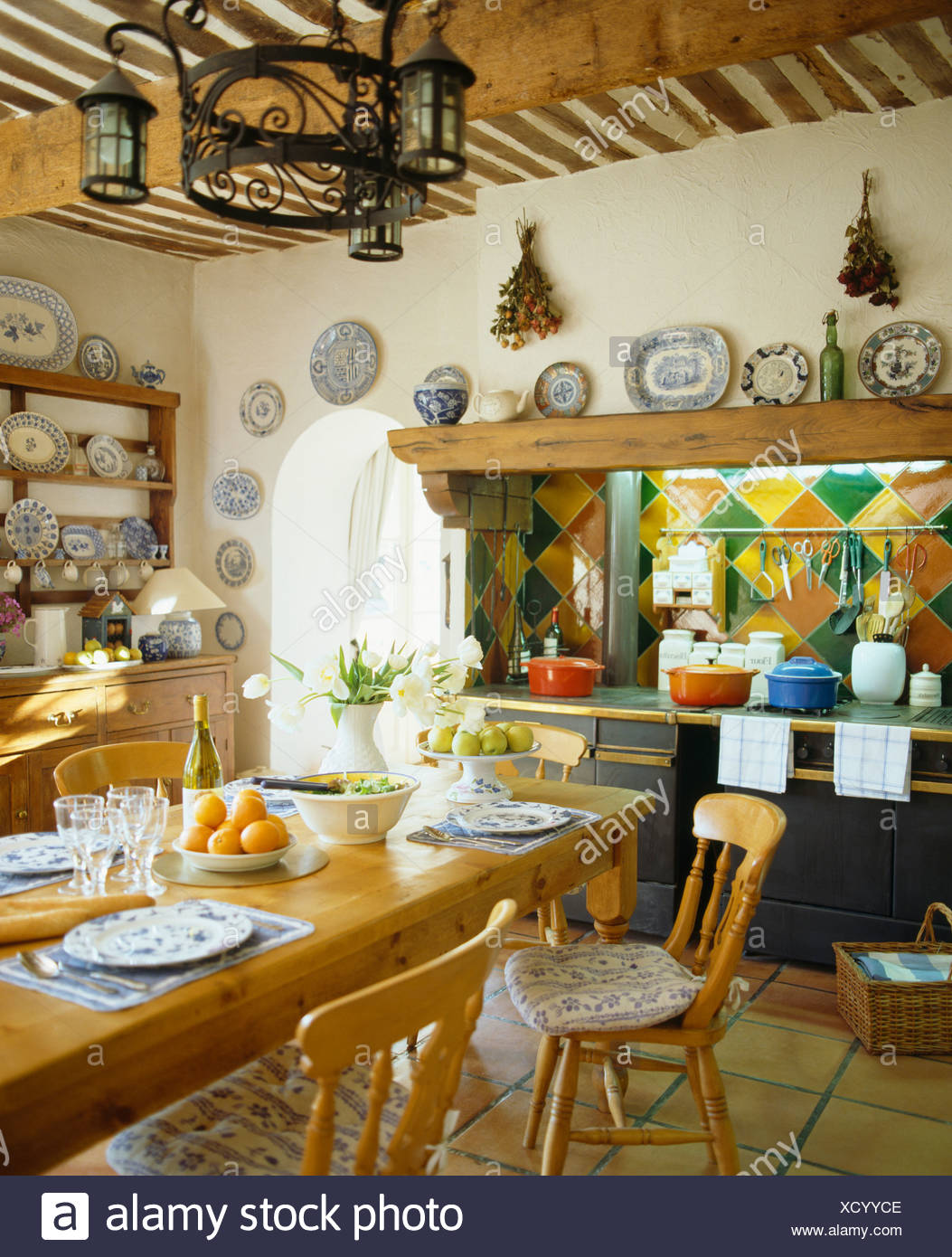 Lantern light fitting above pine chairs and table set for lunch in french country kitchen with colorful tiles above range oven