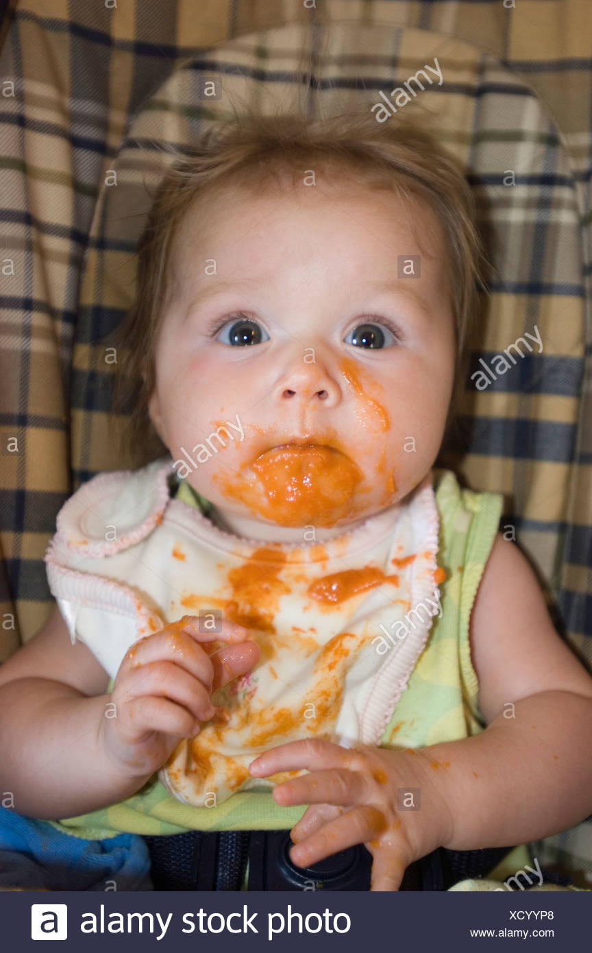 A 4-month-old baby girl, eating squash and making a mess
