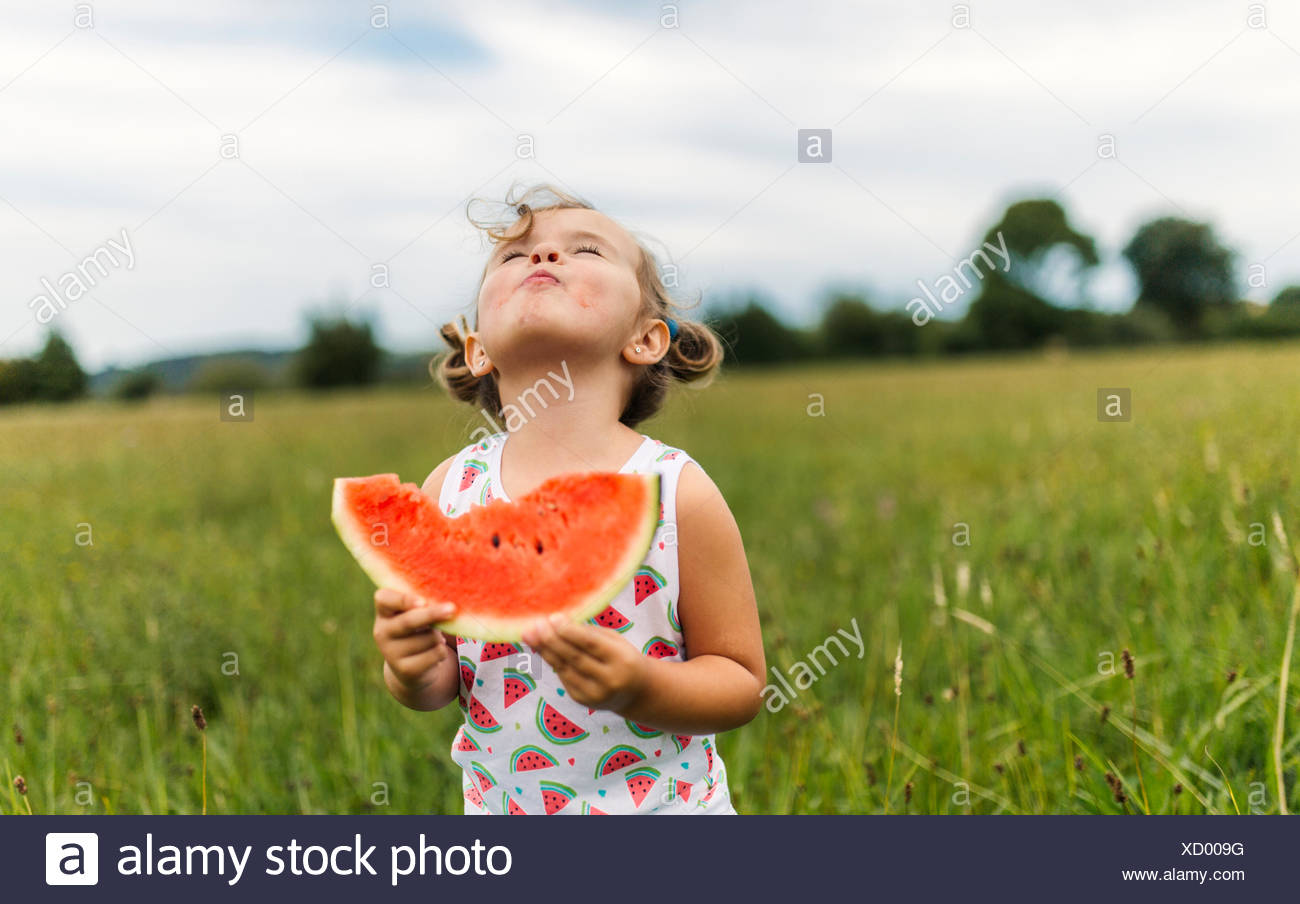 Little girl eating watermelon on a meadow - Stock Image