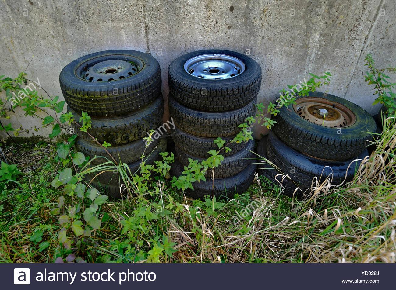 Old car tires between nettles, Schaeftlarn, Bavaria - Stock Image
