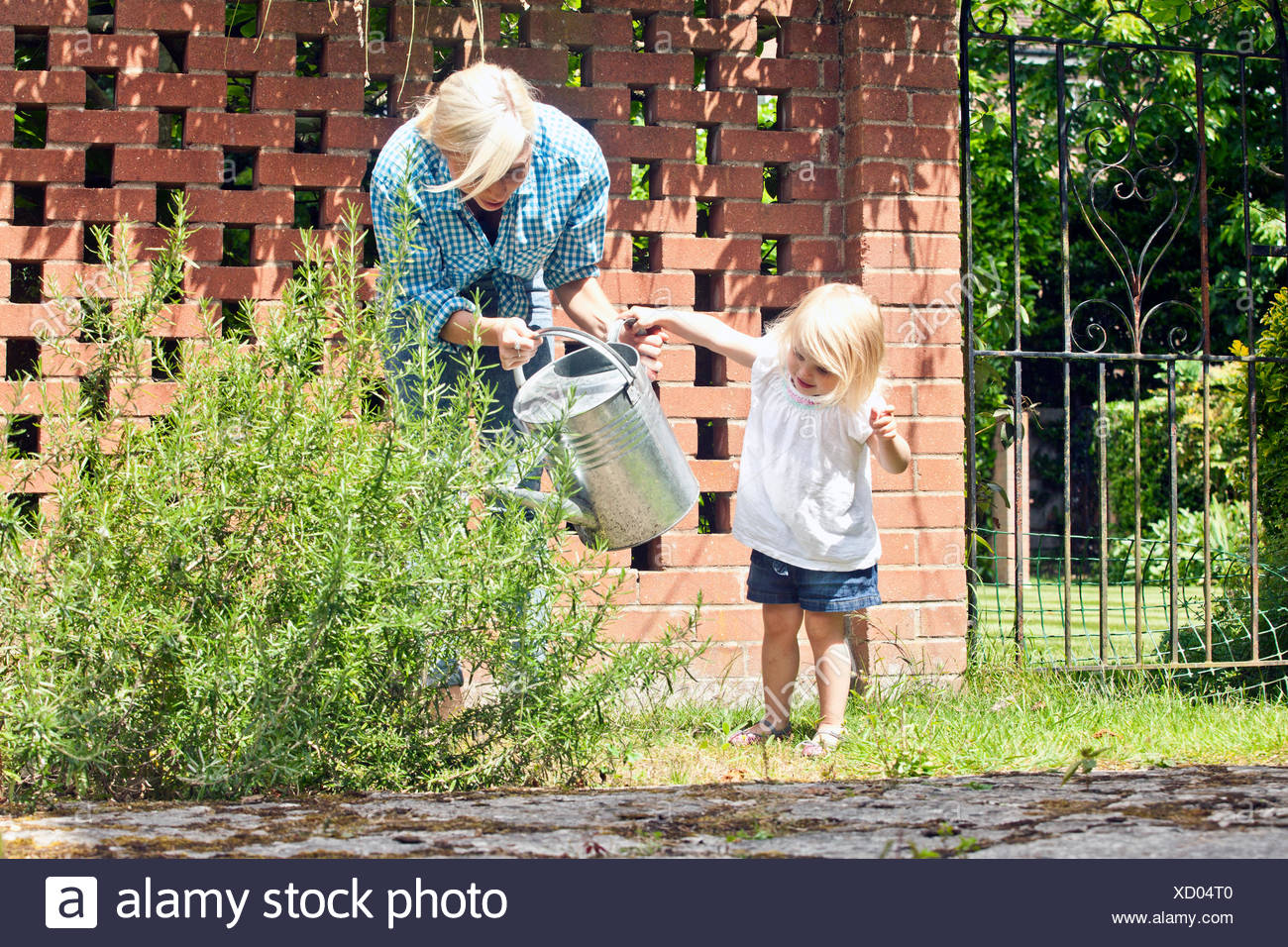 Female toddler helping mother with watering can in garden - Stock Image