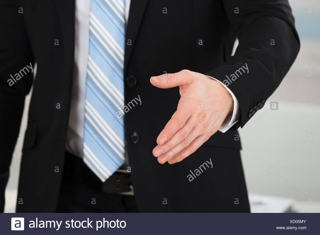 Businessman Offering Handshake In Office - Stock Image