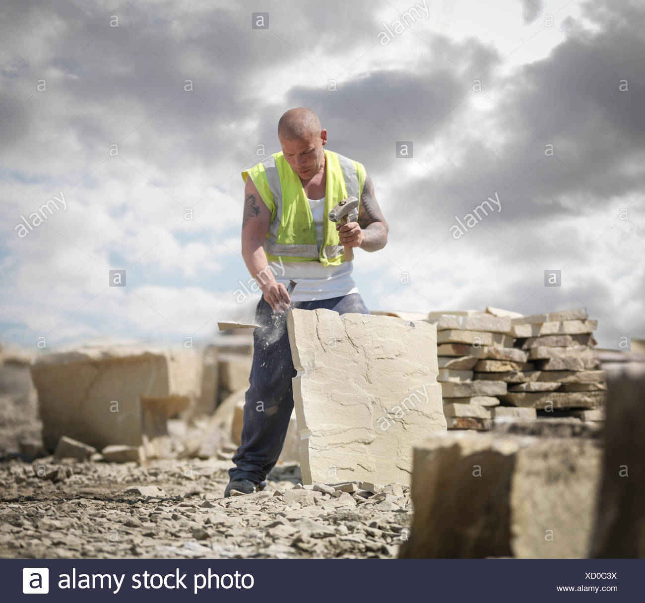 Quarry worker shaping sandstone in Yorkshire stone quarry - Stock Image