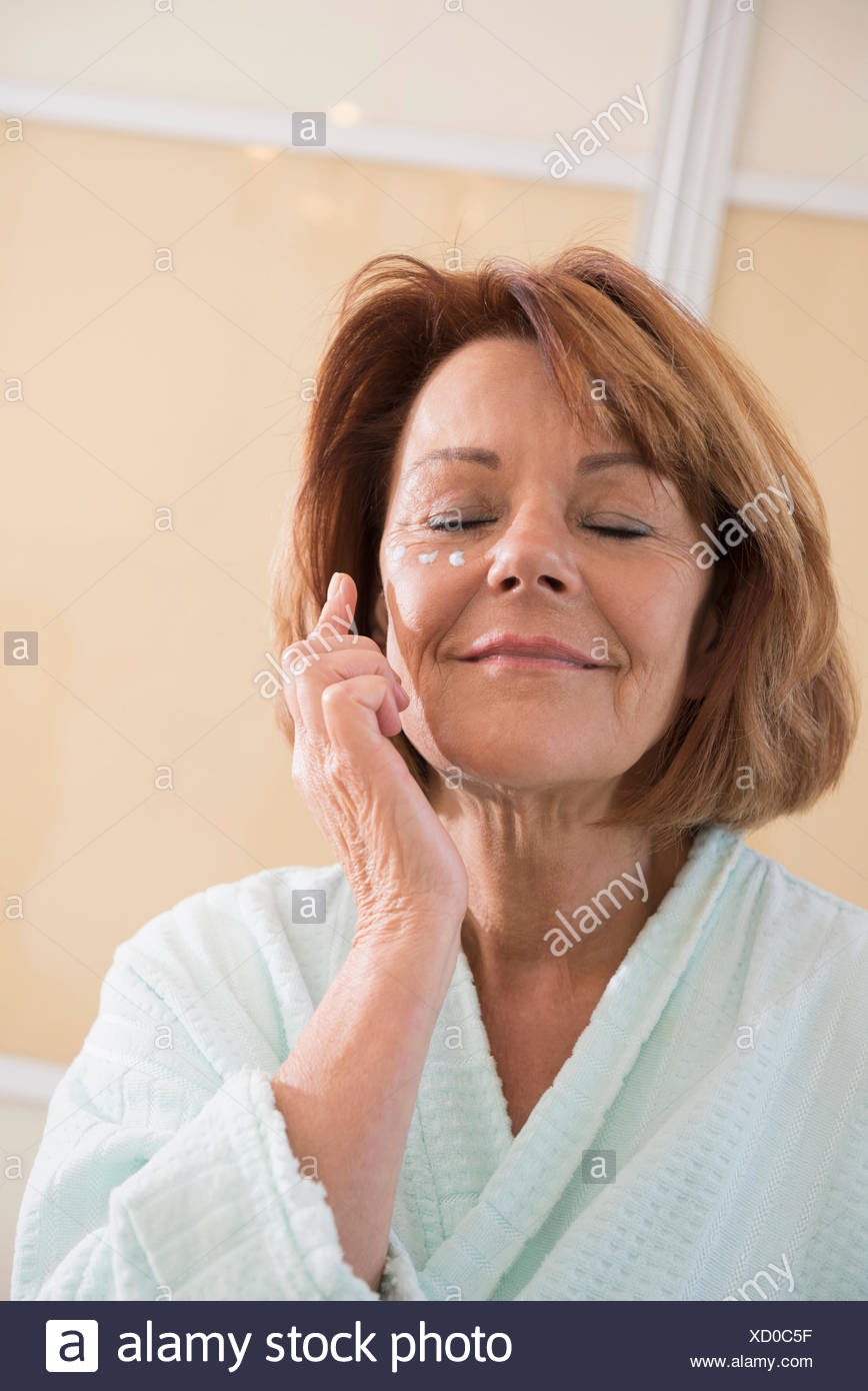 Senior woman applying moisturizer on her face, Munich, Bavaria, Germany - Stock Image