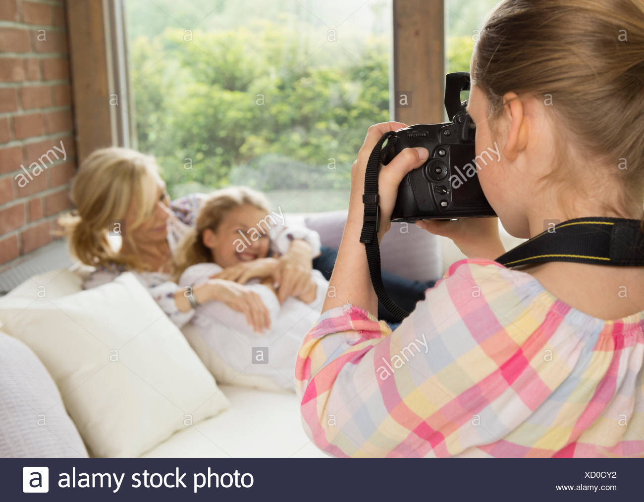 Daughter taking photograph of mother and sister - Stock Image