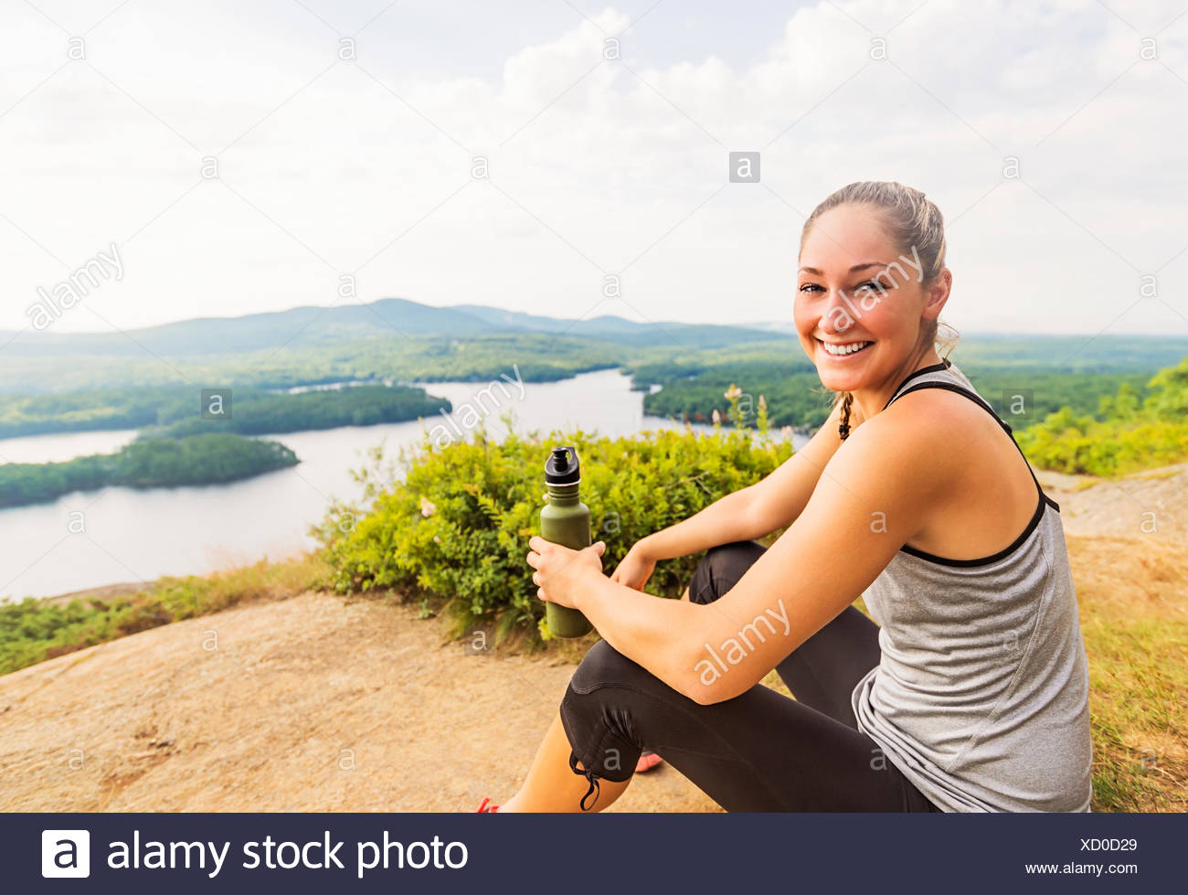 Smiling young female hiker resting - Stock Image