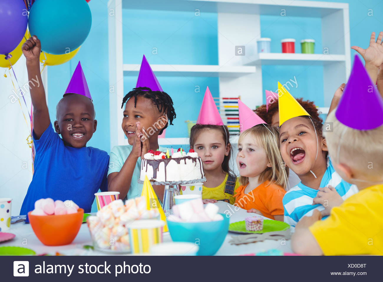 Excited kids enjoying a birthday party - Stock Image