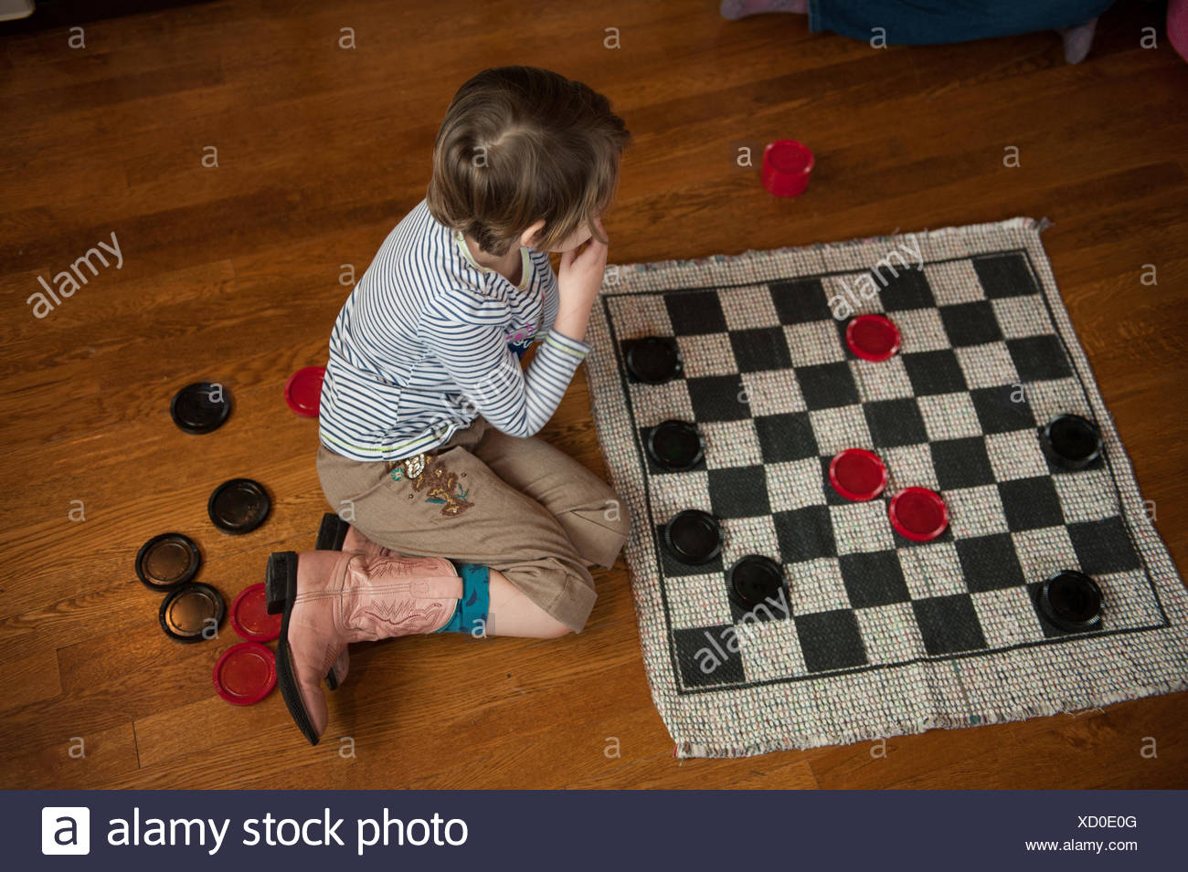 Girl sitting on wooden floor playing draughts - Stock Image