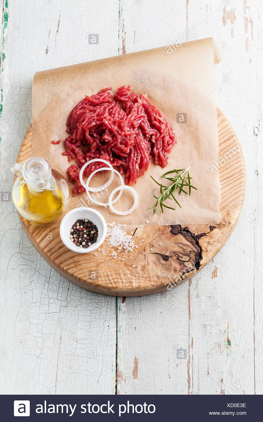 Fresh minced meat with onion and spices on wooden cutting board on blue background Stock Photo