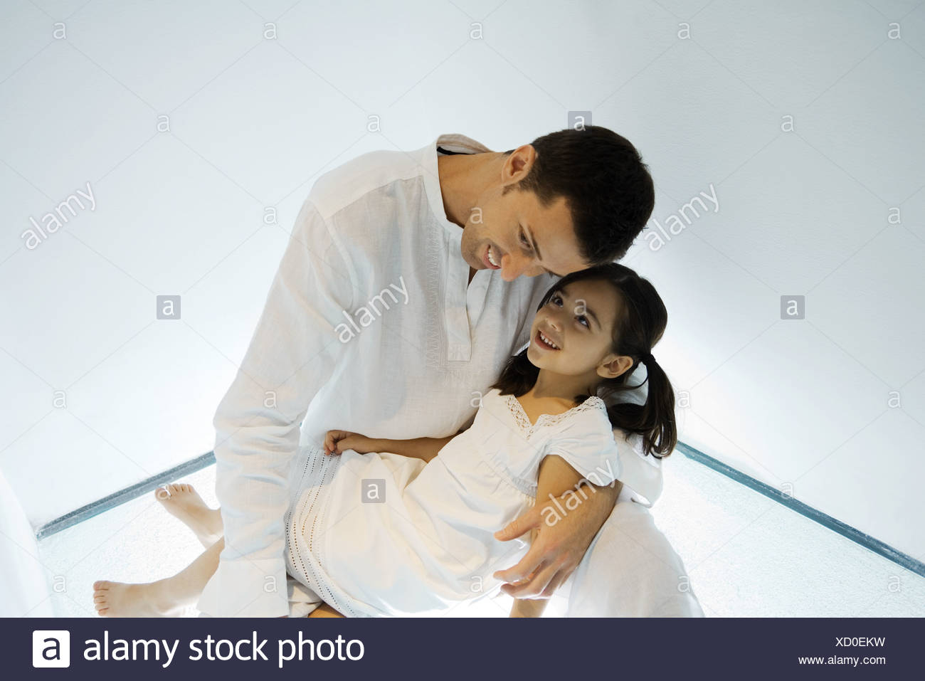 Father holding daughter on lap, leaning head toward her face - Stock Image