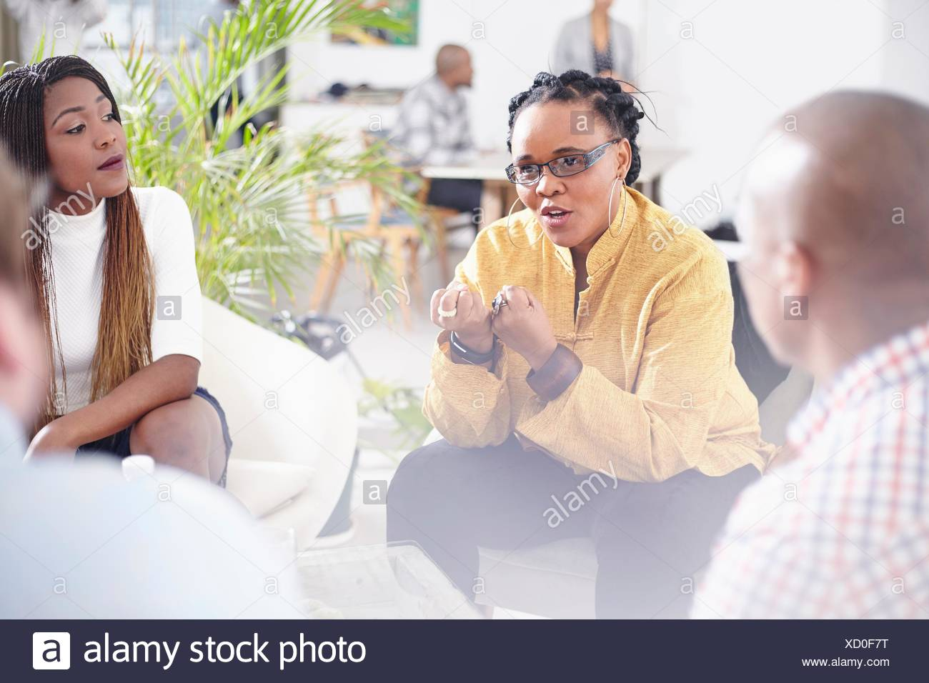 Mature woman talking to colleagues, hand gestures - Stock Image