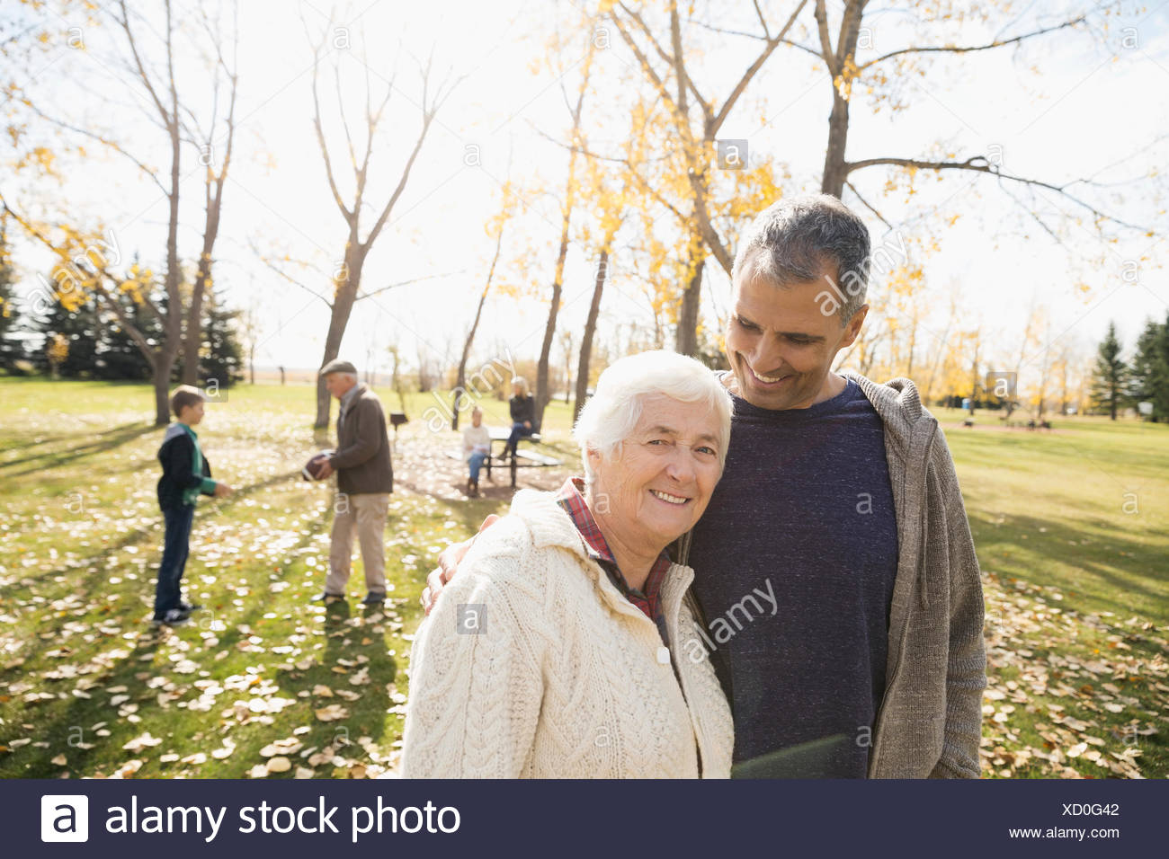 Portrait smiling mother and son in sunny autumn park - Stock Image