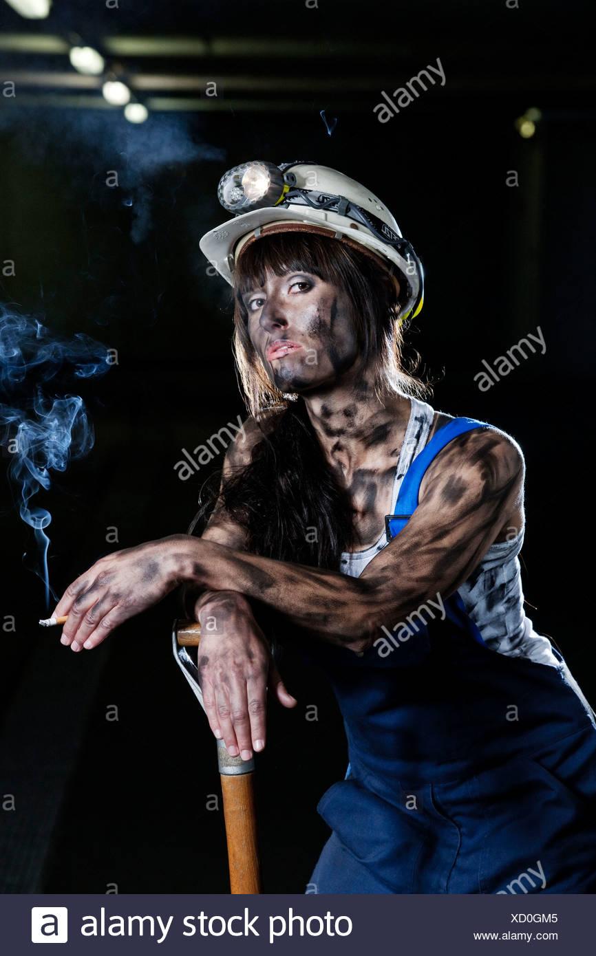 Female mine worker holding a cigarette, Innsbruck, Tyrol, Austria - Stock Image