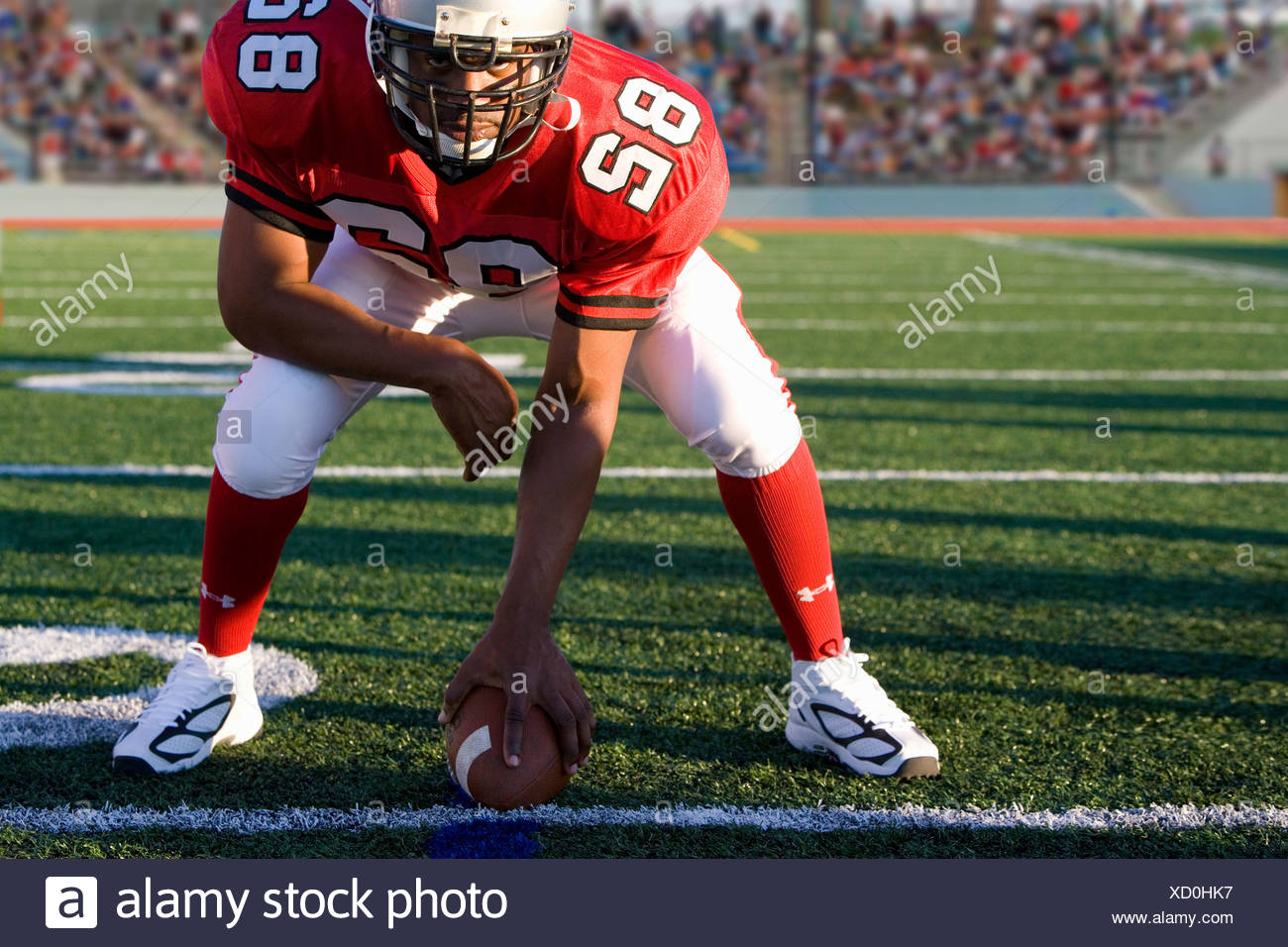 Center poised to snap football on field - Stock Image