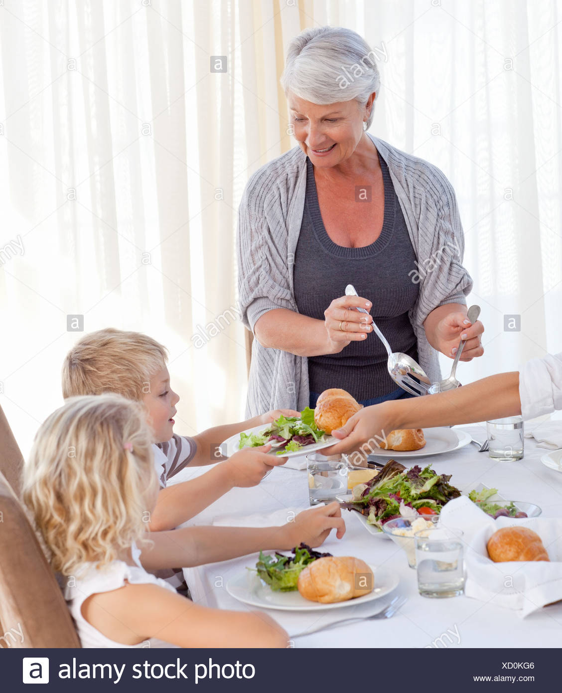 Grandmother giving other family members some food during the meal - Stock Image