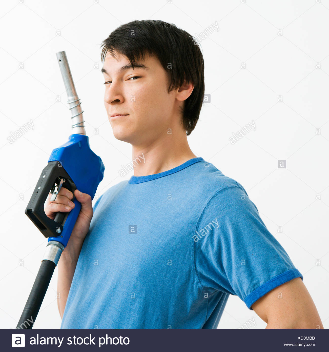 Asian young man holding gasoline pump nozzle - Stock Image