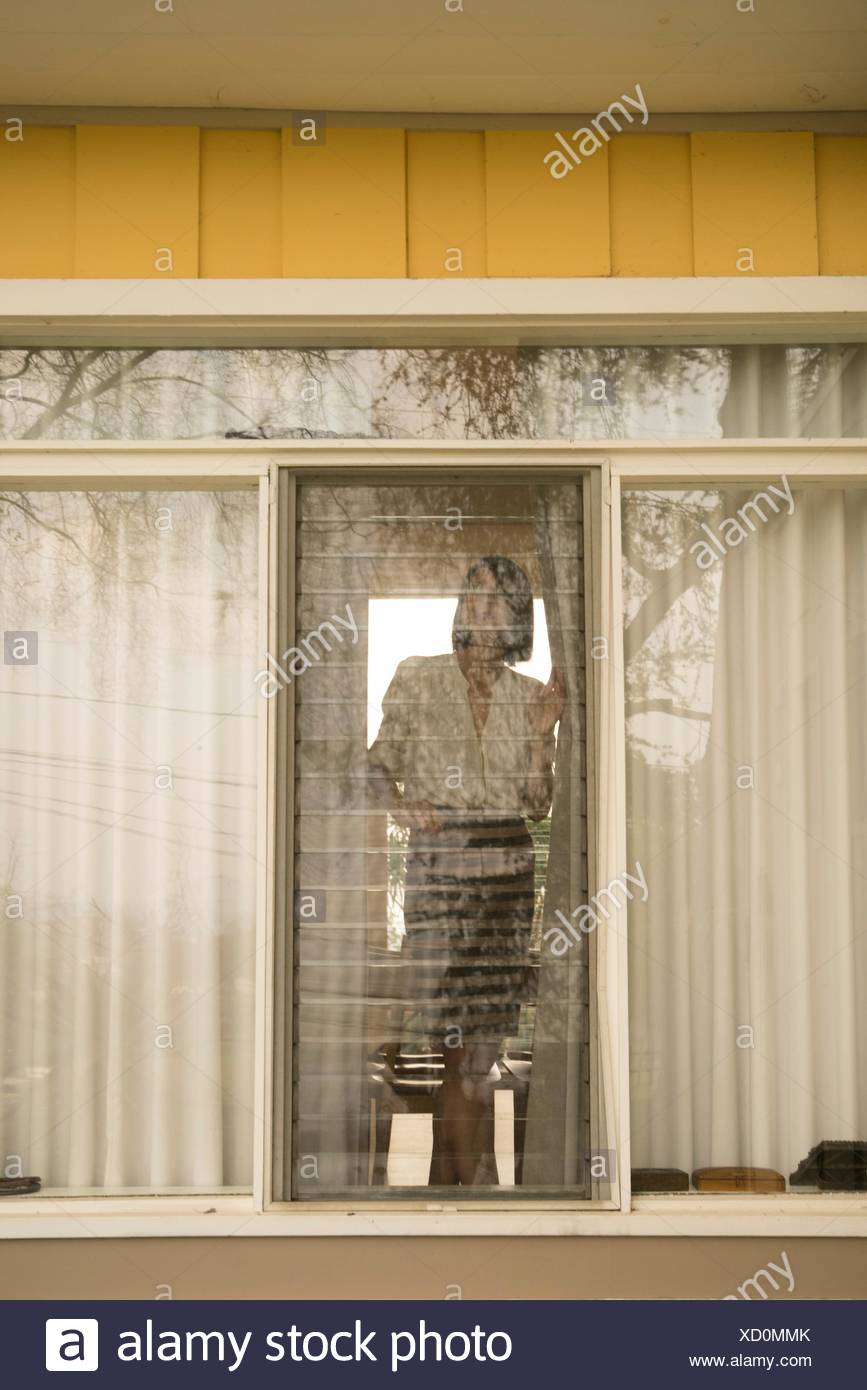 Woman looking out of house window - Stock Image