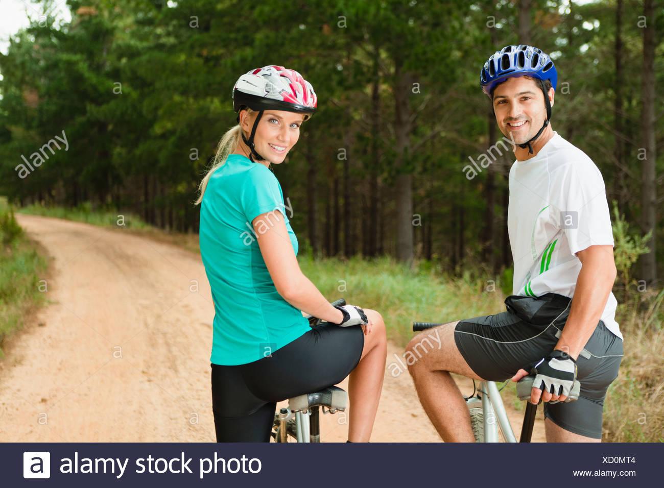 Couple mountain biking on dirt path - Stock Image