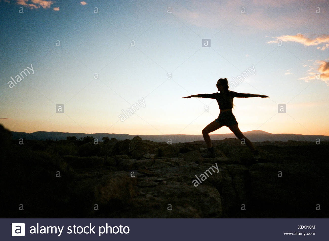 Silhouette of woman in yoga pose - Stock Image