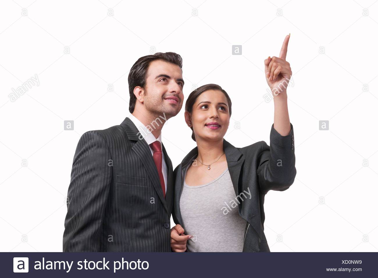 Smiling businesswoman showing something to colleague against white background - Stock Image