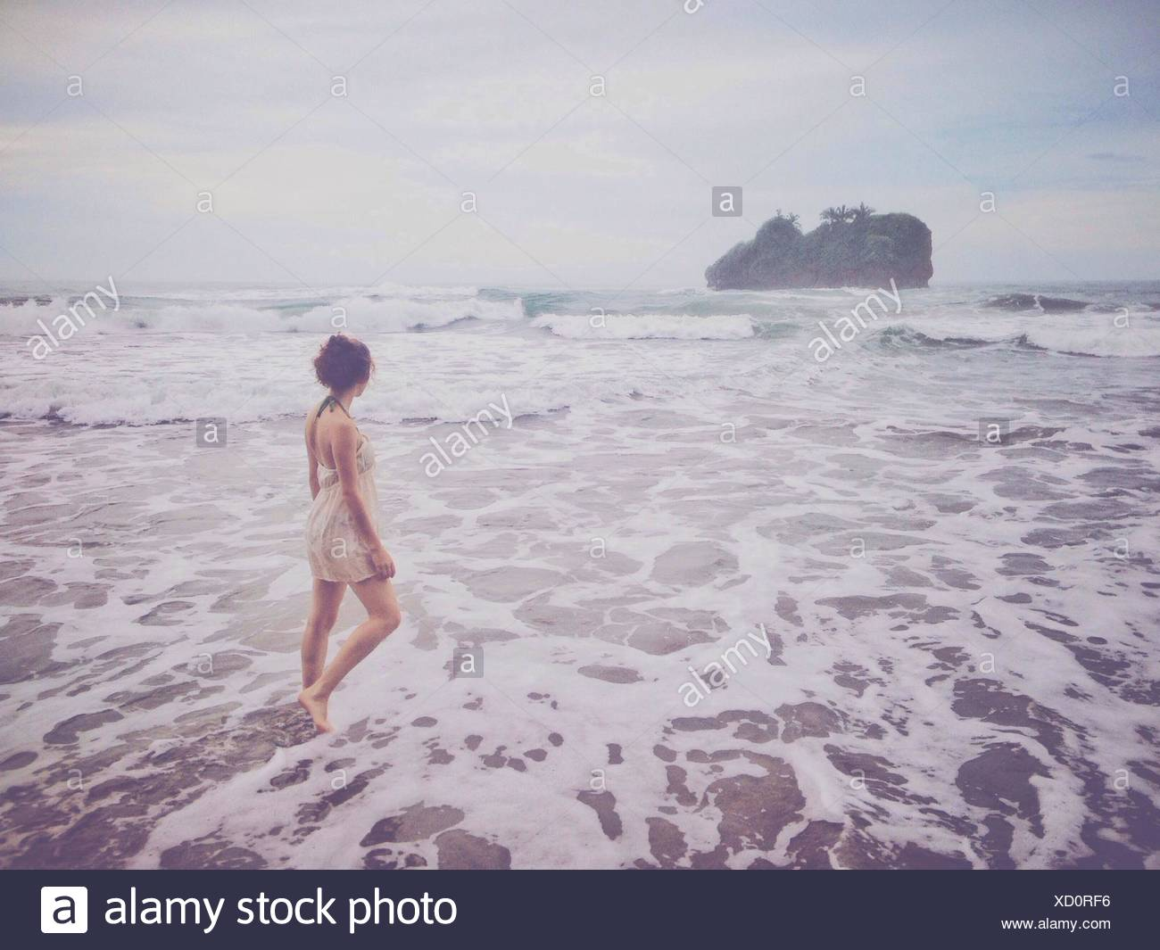 Rear View Of Young Woman Walking In Water At Beach - Stock Image