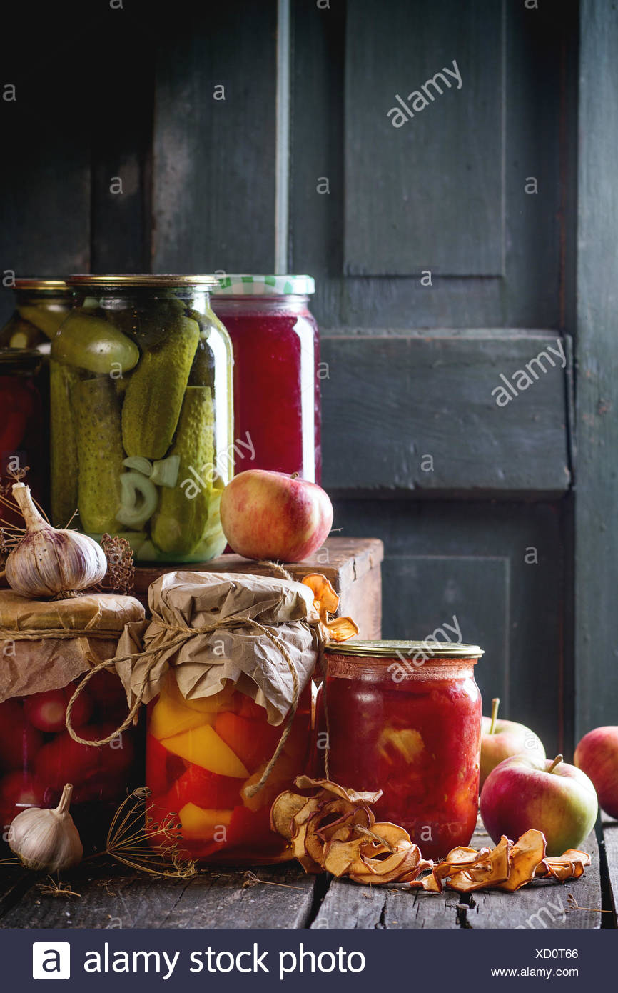 Collection set of many homemade glass jars with preserved food (cucumbers, tomatoes, peppers), with garlic and fresh and dried a - Stock Image