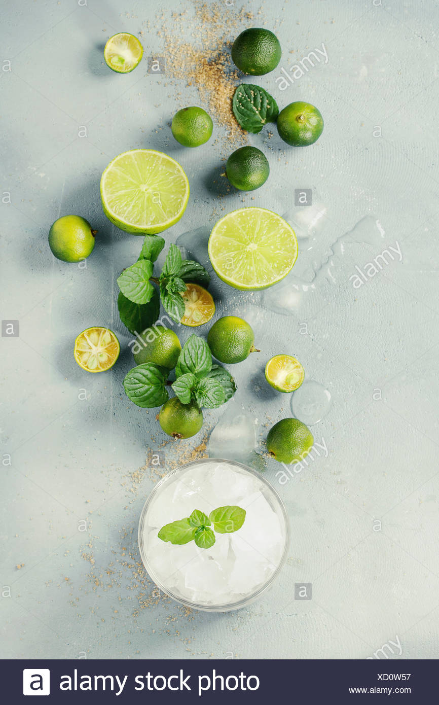 Ingredients for mojito cocktail, whole, sliced lime and mini limes, mint leaves, brown crystal sugar over gray stone texture background with glass ful - Stock Image