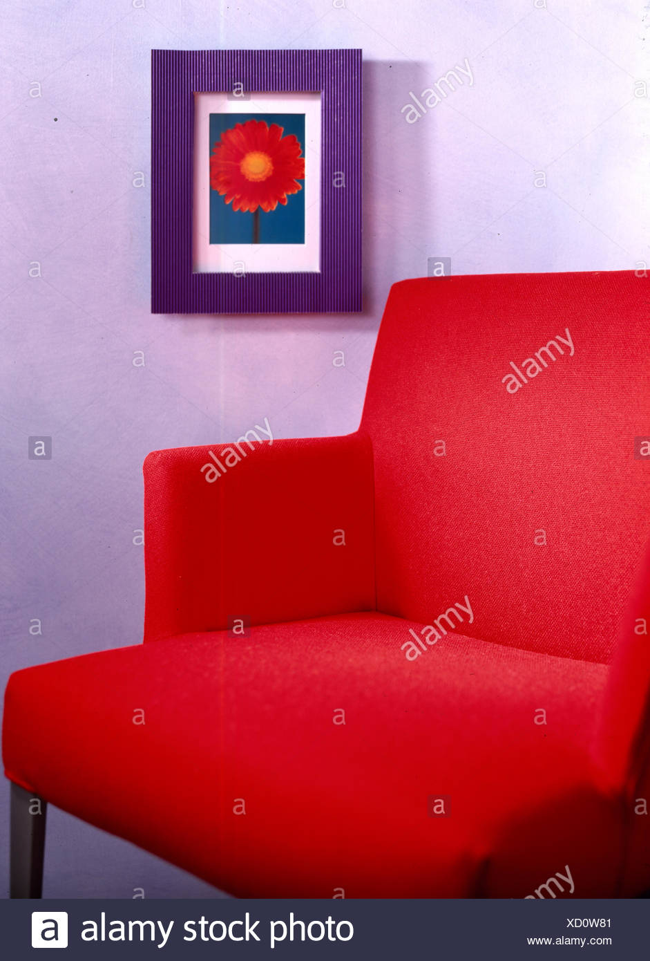 Closeup Of Red Upholstered Chair In Front Of Framed Flower Print
